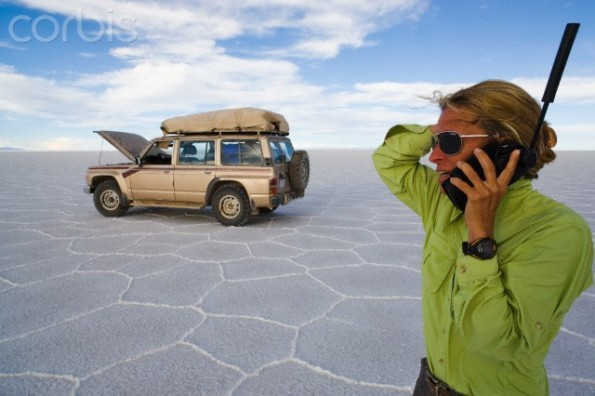 Woman talking on satellite phone near broken down SUV